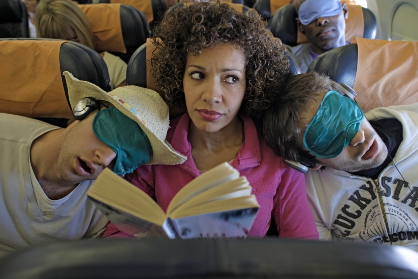 A woman sitting between two impolite male passengers (Getty Images)