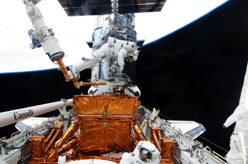 In this handout from NASA, STS-125 mission specialists astronaut Michael Good (L) and astronaut Mike Massimino participate in the mission's fourth spacewalk to repair the Hubble Space Telescope (NASA via Getty Images)