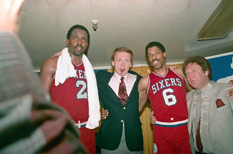 (Original Caption) Philadelphia 76ers' Moses Malone (2) and Julius Erving (6) hug their coach Bill Cunninham in the dressing room after the 76ers made a clear 4 game sweep over the Los Angeles Lakers to win the NBA Championship at the Forum 5/31, 115-108.