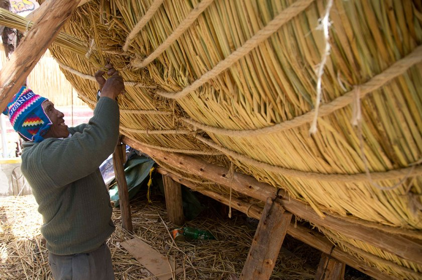 """Seventy-one-year-old Juan Limachi, who has been building reed boats since the age of seven using the technology inherited from his Aymara ancestors, works on the """"Viracocha III,"""" in La Paz, Bolivia, Wednesday, Oct. 19, 2016. (Juan Karita/AP)"""