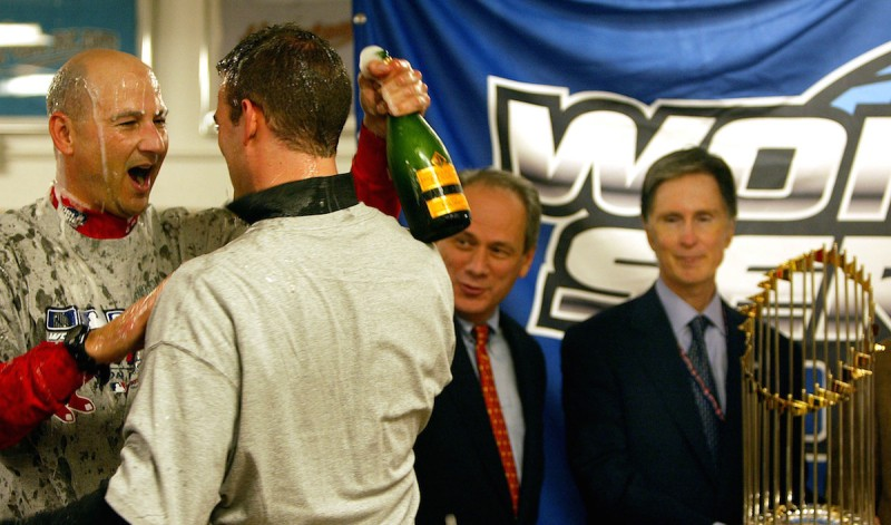 ST. LOUIS - OCTOBER 27: Terry Francona, Theo Epstein, Larry Lucchino, and John Henry with the trophy in the locker room. (Photo by Jim Davis/The Boston Globe via Getty Images)
