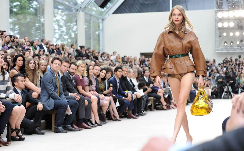 LONDON, ENGLAND - SEPTEMBER 17: Julian Ovenden, Pete Reed, Saif Ali Khan, Alice Eve, Victoria Pendleton, Aaron Paul, Dita Von Teese, Harry Styles, Dev Patel, Gabriella Wilde, Mario Testino, Harvey Weinstein and Sir Jonathan Ive watch from the front row as model Cara Delevingne walks the runway during the Burberry Spring Summer 2013 Womenswear Show at Kensington Gardens on September 17, 2012 in London, England. (Photo by Dave M. Benett/Getty Images for Burberry)