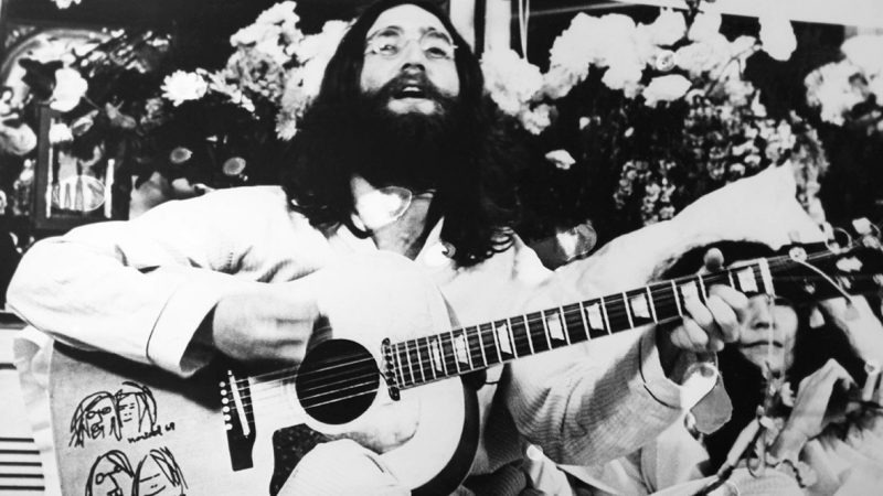 CANADA - 1969: John Lennon with beard and long hair singing and playing guitar in 1969 in Canada. (Photo by Keystone-France/Gamma-Rapho via Getty Images)