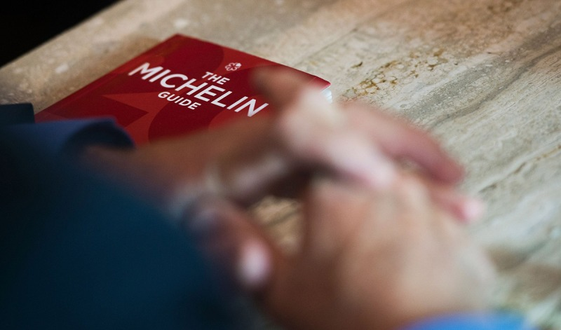 """Michael Ellis from Michelin poses with the Michelin guide book at a restaurant in Washington, DC on October 12, 2016. The Michelin Guide unveiled its first edition for the US capital Washington on Thursday, awarding coveted stars to a dozen restaurants it said were part of a hot foodie scene. Alas, no restaurant got the full blessing of three stars, although three received two stars and nine got one. / AFP / Andrew CABALLERO-REYNOLDS / TO GO WITH AFP STORY BY ELODIE CUZIN- """"Michelin unveils Washington guide, no three-star eateries"""" (Photo credit should read ANDREW CABALLERO-REYNOLDS/AFP/Getty Images)"""