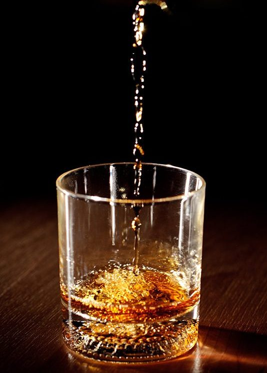 Scotch or bourbon whiskey (or whisky) being poured into a glass with dramatic studio lighting and a black background. (Getty Images)