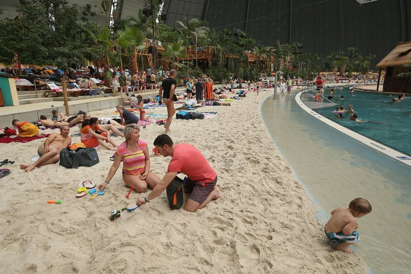 "KRAUSNICK, GERMANY - FEBRUARY 15: A couple from the east German city of Chemnitz lounge with their son at the ""South Sea"" beach at the Tropical Islands indoor resort on February 15, 2013 in Krausnick, Germany. Located on the site of a former Soviet military air base, the resort occupies a hangar built originally to house airships designed to haul long-distance cargo. Tropical Islands opened to the public in 2004 and offers visitors a tropical getaway complete with exotic flora and fauna, a beach, lagoon, restaurants, water slide, evening shows, sauna, adventure park and overnights stays ranging from rudimentary to luxury. The hangar, which is 360 metres long, 210 metres wide and 107 metres high, is tall enough to enclose the Statue of Liberty. (Photo by Sean Gallup/Getty Images)"