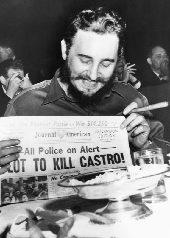 """(Original Caption) Seems amused by assassination plot...Seeming quite amused, Cuban Prime Minister Fidel Castro holds up a newspaper headlining the discovery of a plot to kill Castro here, April 23rd. Castro was at the Overseas Press Club at the time. Police said five brothers had been sent here from Philadelphia, Pa., to assassinate the bearded leader. Police said that three other men, including a sixth brother, were believed to be in New York in connection with the plot to kill Castro. Earlier in the day, when asked about a reported assassination attempt, Castro had replied, """"In Cuba, they had tanks, planes and they run away. So what are they going to do here? I sleep well and don't worry at all."""" (Bettmann/Contributor/Getty Images)"""