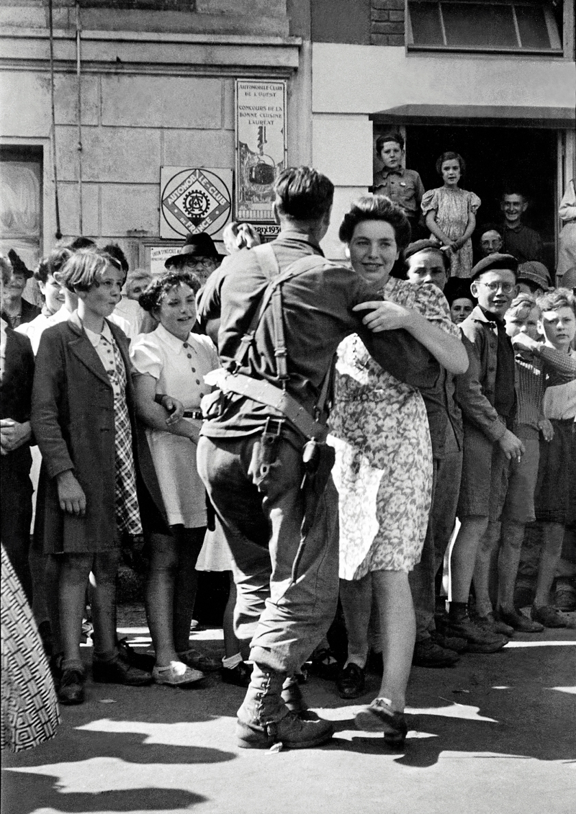 An American GI dances with Marie-Therese Crochu in Saint-Briac-sur-Mer, France, World War II, after the liberation of the town, 15th August 1944. French children Monique Rault and Josette Joly can be seen on the right, Rene Gesse on the left. (Tony Vaccaro/Getty Images)