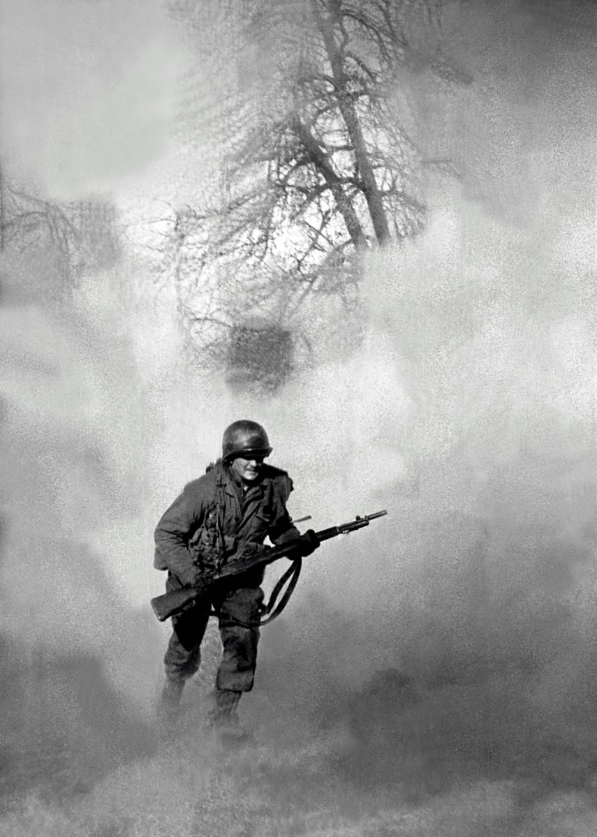 American GI Ivan Parrott is seen running through smoke in no mans land near Neuss, Germany during the Battle for the Rhine, World War II, 1st March 1945. (Tony Vaccaro/Getty Images)