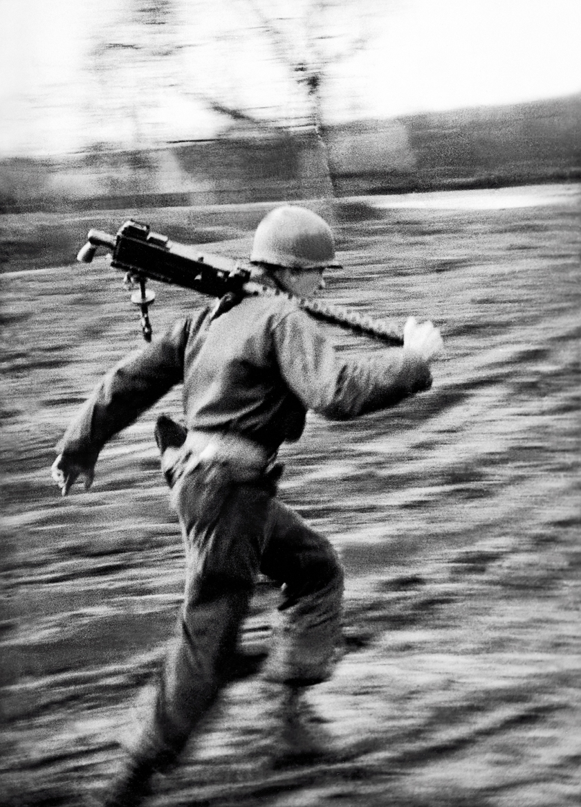 An American GI runs with a machine gun during the Battle of the Bulge, Ardennes, Belgium, World War II, January 1945. (Tony Vaccaro/Getty Images)
