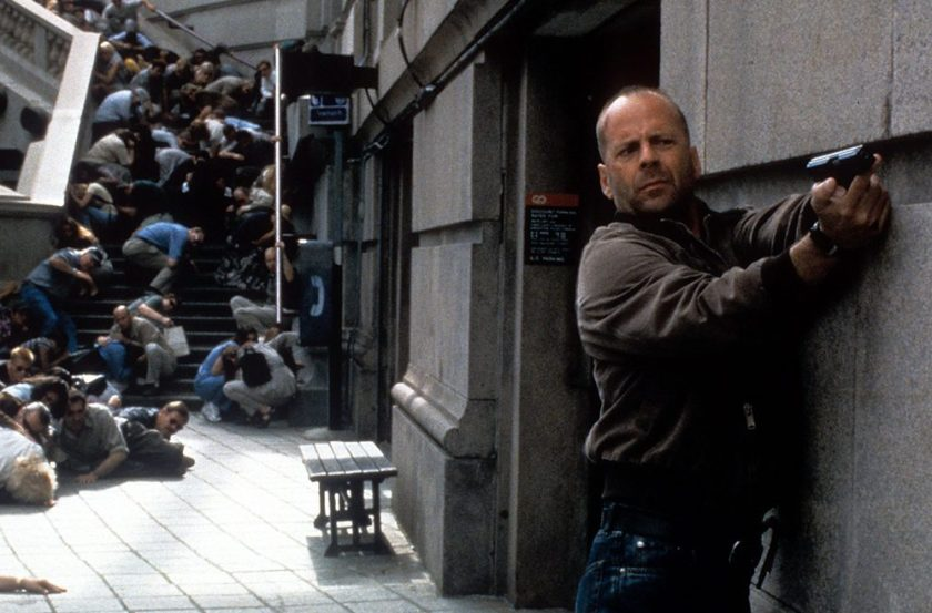 Bruce Willis aims a gun as others duck for cover in a scene from the film 'Mercury Rising,' 1998. (Universal/Getty Images)