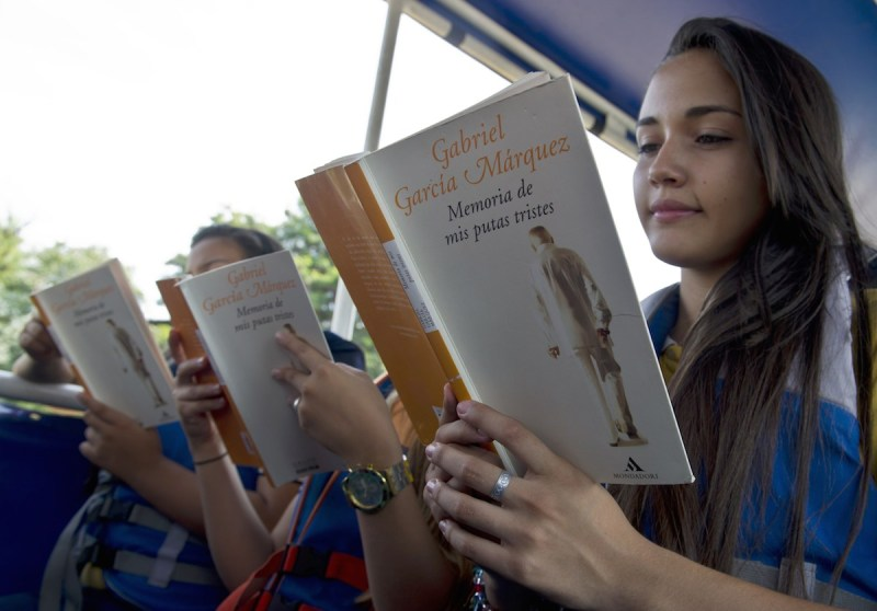 """Students read the novel """"Memoria de mis putas tristes"""" (Memories of My Melancholy Whores) by late Nobel Prize laureate in Literature Gabriel Garcia Marquez, in Cali, department of Valle del Cauca, Colombia on April 25, 2014, during a day of reading on the Cauca river, aboard the boat school of the environmental institution CVC (Corporacion Autonoma Regional del Valle del Cauca). AFP PHOTO/Luis ROBAYO (Photo credit should read LUIS ROBAYO/AFP/Getty Images)"""