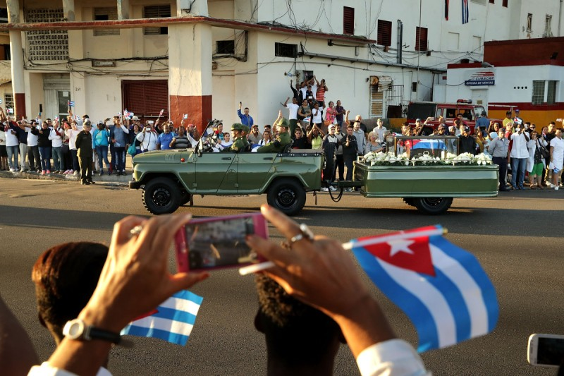 A military truck pulls a trailer with the flag-draped chest that holds the remains of former President Fidel Castro as thousands of Cubans line the famous Malecon seaside boulevard to pay their respects (Chip Somodevilla/Getty Images)