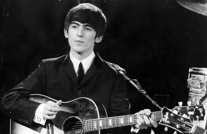 3rd December 1963: Guitarist and singer George Harrison (1943 - 2001) of the popular Merseybeat group The Beatles, performing during a live concert. (Fox Photos/Getty Images)