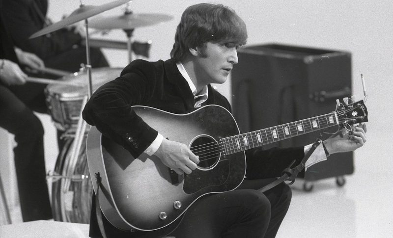 "UNSPECIFIED - CIRCA 1960: Photo of BEATLES and John LENNON; of the Beatles, tuning guitar (Gibson J160E acoustic) during the filming of ""A Hard Day's Night"" at the Scala Theatre (Max Scheler - K & K/Redferns)"