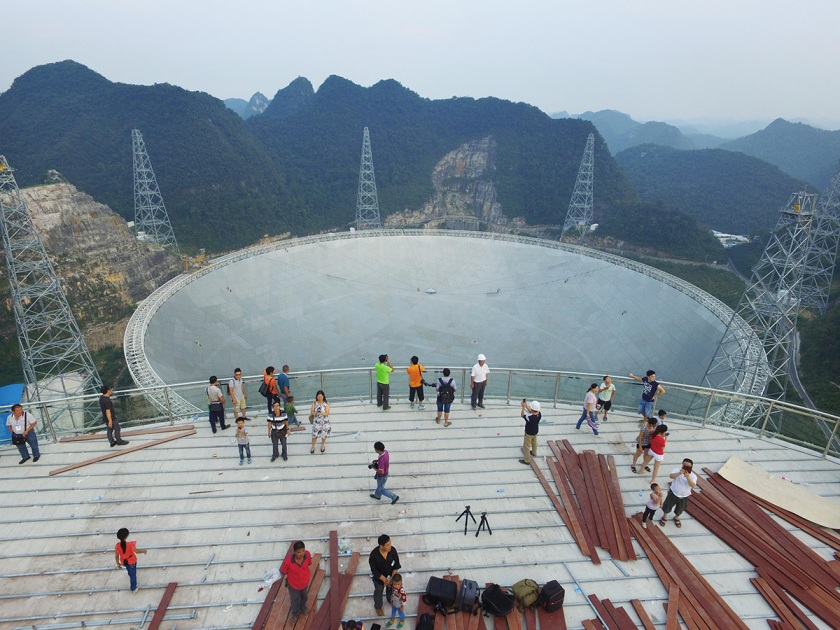 Aerial view of tourists looking at a dish-like radio telescope at Pingtang County on September 17, 2016, in Qiannan Buyei and Miao Autonomous Prefecture, Guizhou Province of China. After five years' construction, the 1,640-foot Aperture Spherical Telescope' (FAST) was put into use on Sept. 25. VCG/VCG via Getty Images)