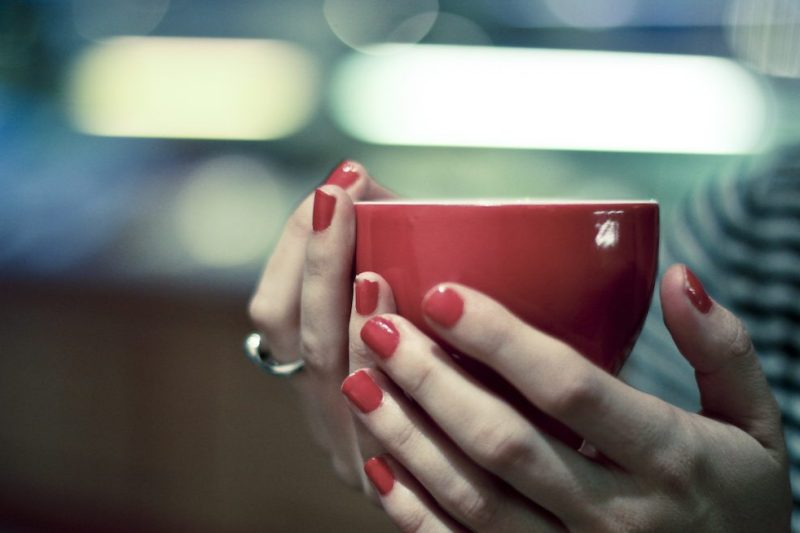 Girl holds red coffee cup.