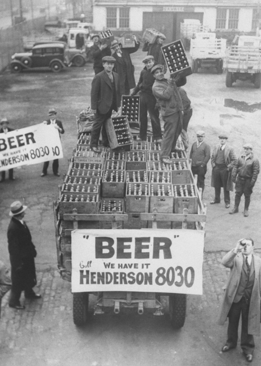 Men atop beer delivery truck hoist cases of beer triumphantly while man standing in front of truck drinks out of beer bottle following the repeal of Prohibition.  (Time Life Pictures/National Archives/The LIFE Picture Collection/Getty Images)