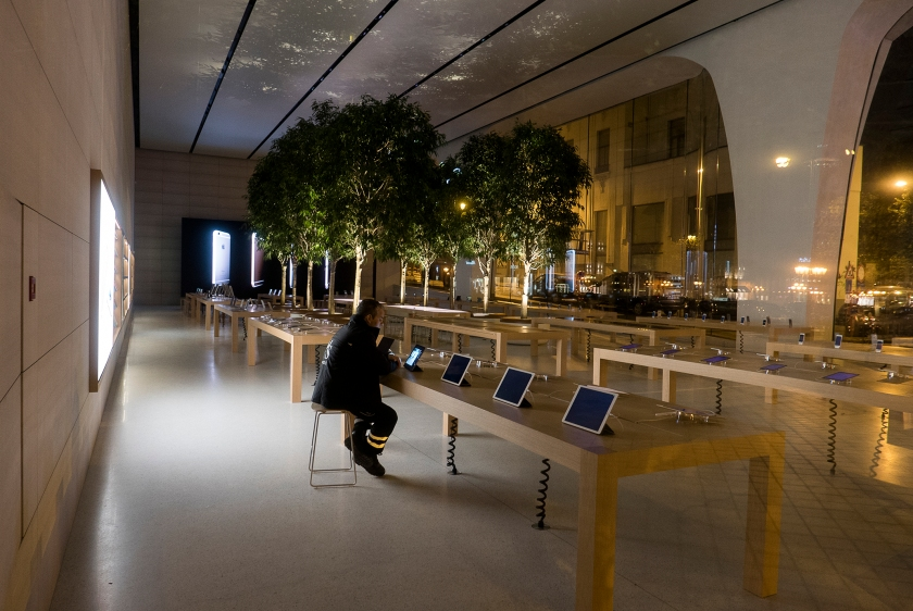 A security officer on duty is looking at Apple product in the Brussels Apple store at night. (Thierry Tronnel/Corbis via Getty Images)