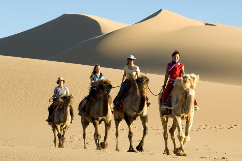 A family rides with a Mongolian guide through the Khongoryn Els sand dunes. The dunes are the most famous feature of Gobi Gurvansaikhan National Park in Mongolia. (Getty Images)
