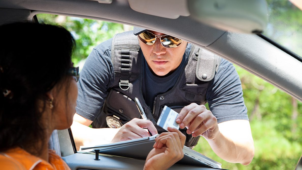 A police officer stops a driver to give her a traffic ticket for speeding. (Getty Images)