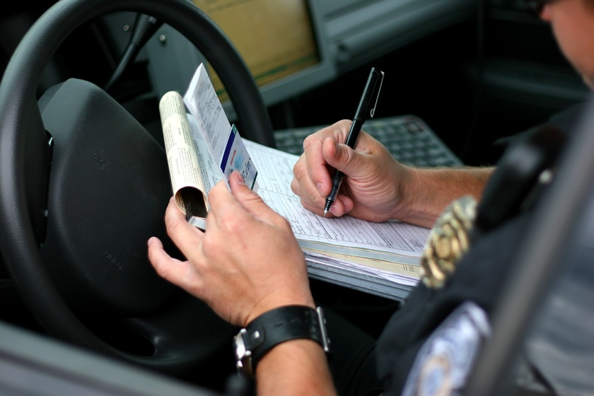 A police officer writes a traffic ticket. (Getty Images)