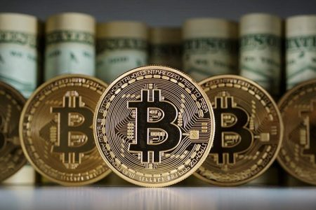 BERLIN, GERMANY - FEBRUARY 15:  In this photo illustration model Bitcoins standing in front of Dollar bills on February 15, 2016 in Berlin, Germany. (Photo Illustration by Thomas Trutschel/Photothek via Getty Images)