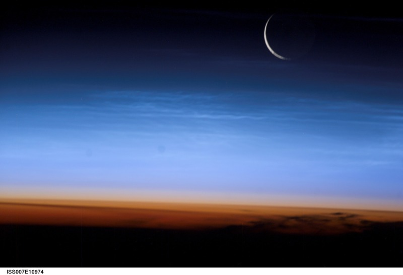 Silvery-blue noctilucent clouds extend far above the Earth's troposphere. The sliver of the setting moon is visible at upper right (NASA/Getty Images)