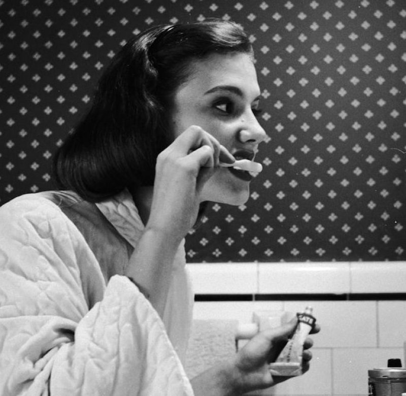 circa 1955: A young woman brushing her teeth in her bathroom. (Photo by Three Lions/Getty Images)