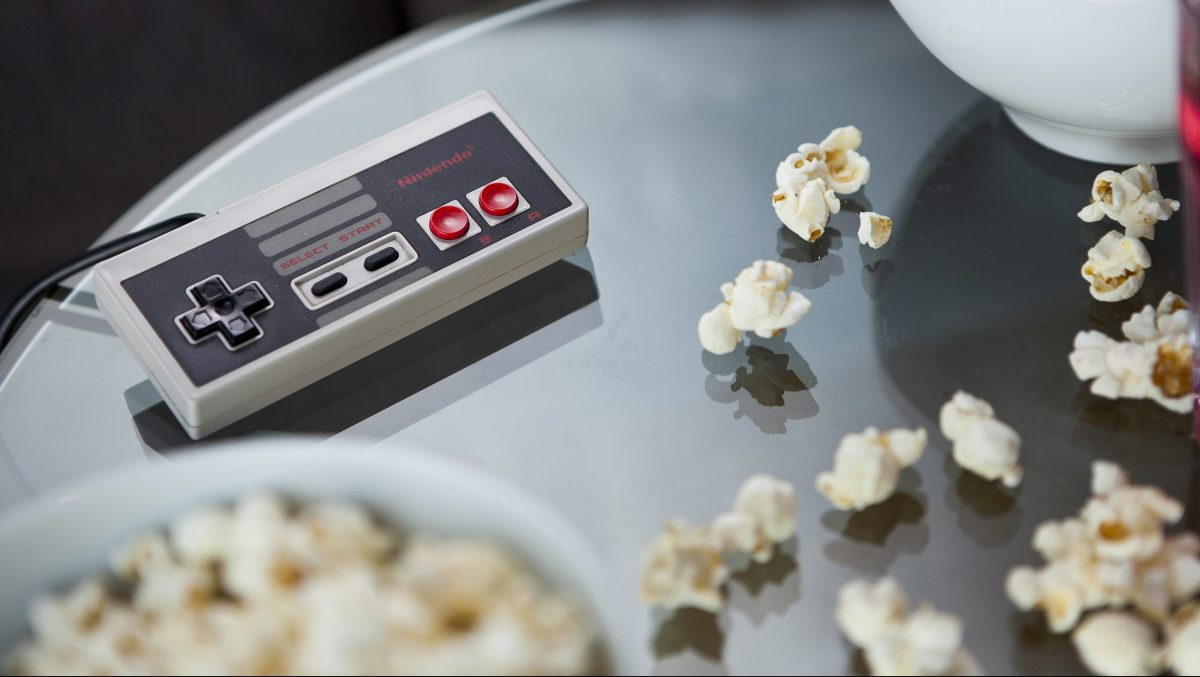 A vintage Nintendo NES controller photographed on a glass table, surrounded by bowls of snacks, taken on July 9, 2013. (Philip Sowels/Future Publishing via Getty Images)