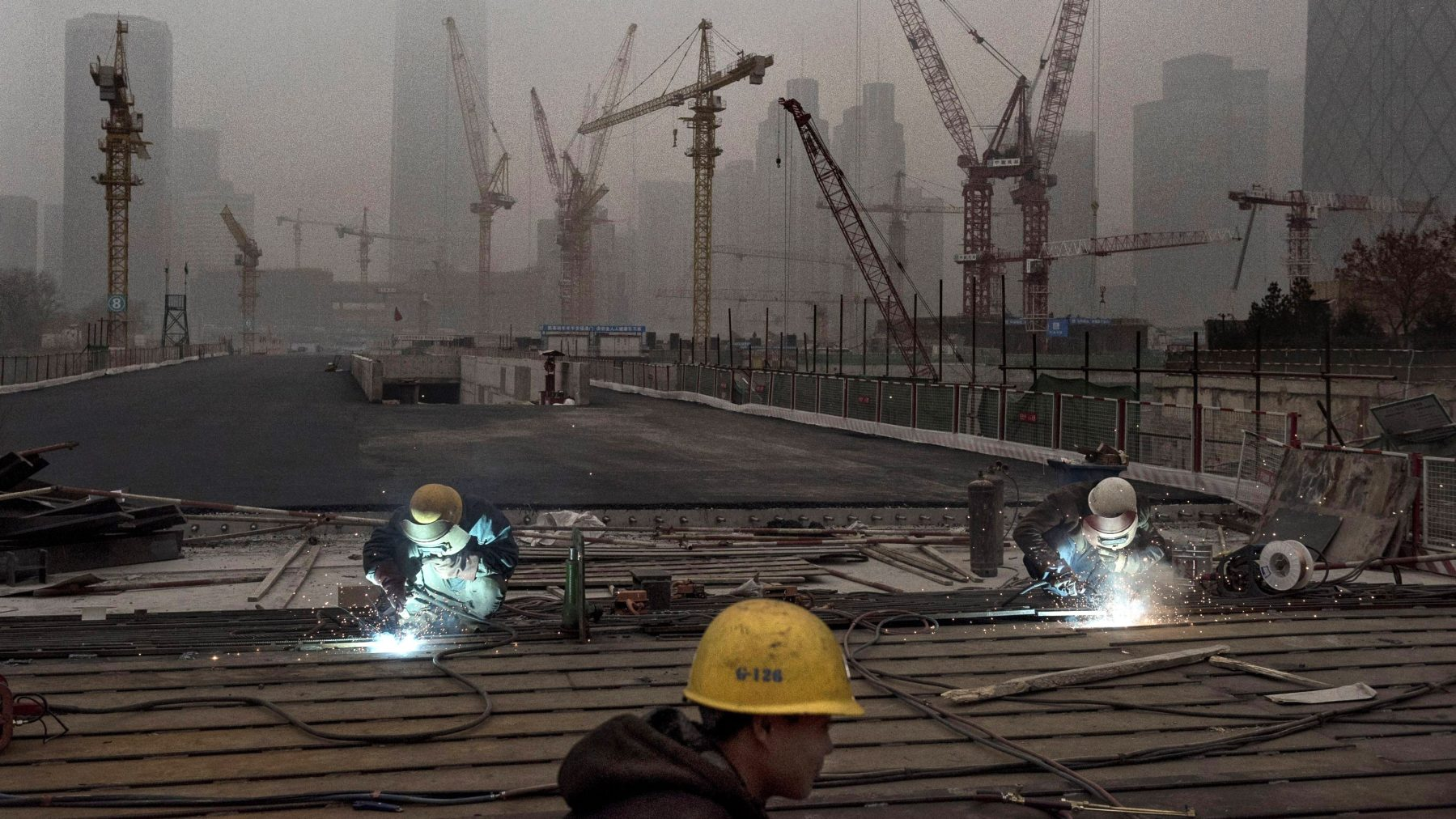 Chinese workers weld at a construction site in heavy pollution on November 29, 2014 in Beijing, China. United States President Barack Obama and China's president Xi Jinping agreed on a plan to limit carbon emissions by their countries, which are the world's two biggest polluters, at a summit in Beijing earlier this month.  (Kevin Frayer/Getty Images)