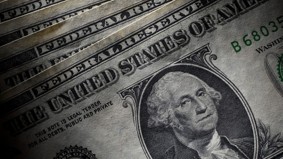U.S. Dollar bills are arranged for a photograph in New York, U.S., on Tuesday, July 26, 2011.The dollar slid to a record low versus the Swiss franc, stocks fell and the cost of insuring U.S. debt rose to a 17-month high as Democrats and Republicans continued to wrangle over competing plans to cut the deficit. Photographer: Scott Eells/Bloomberg
