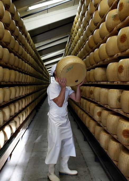 Bloomberg's Best Photos 2014: A worker selects a whole Parmigiano-Reggiano cheese from a storage rack ahead of inspection at Coduro cheesemakers in Fidenza, Italy, on Thursday, Sept. 11, 2014. Russian stores have run out of imported salmon and cheeses such as Parmigiano-Reggiano, Camembert and Brie, leading retailers like Metro AG's Cash & Carry unit to look for replacements, according to an e-mailed statement. Photographer: Alessia Pierdomenico/Bloomberg via Getty Images