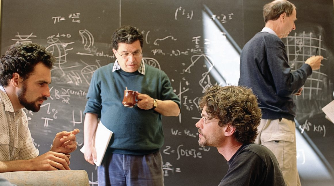 Physicists discuss their work during a coffee break