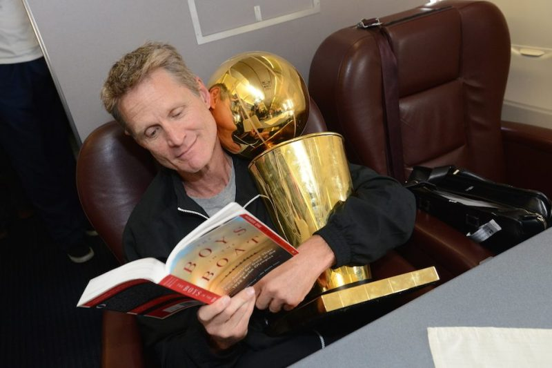 OAKLAND, CA - JUNE 17: Steve Kerr of the Golden State Warriors holds the NBA trophy on the plane as the team travels home from Cleveland after winning the 2015 NBA Finals on June 17, 2015 in Oakland, California. NOTE TO USER: User expressly acknowledges and agrees that, by downloading and/or using this Photograph, user is consenting to the terms and conditions of the Getty Images License Agreement. Mandatory Copyright Notice: Copyright 2015 NBAE (Photo by Noah Graham/NBAE via Getty Images)