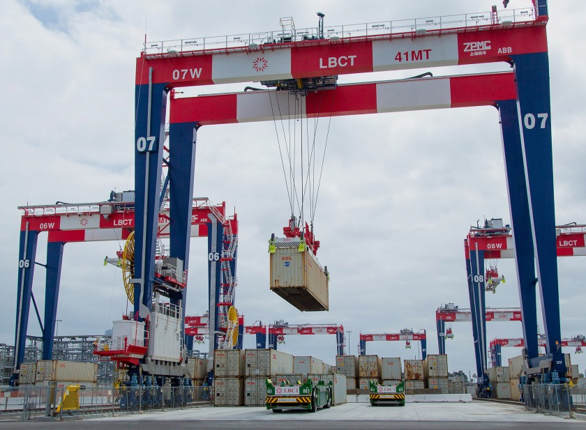 Containers are loaded onto automated guided vehicles (AGV) during the testing phase of the Long Beach Container Terminal in Middle Harbor at the Port of Long Beach in Long Beach, California, U.S., on Wednesday, May 13, 2015. Next year, deckhands on ships docked at Middle Harbor on California's San Pedro Bay won't see many people on the wharf. Remote-controlled cranes towering 165 feet overhead will pluck containers from vessels' holds, and driverless trucks guided by magnets embedded in the asphalt will carry cargo to robotic hoists in a sorting yard. (Tim Rue/Bloomberg via Getty Images)