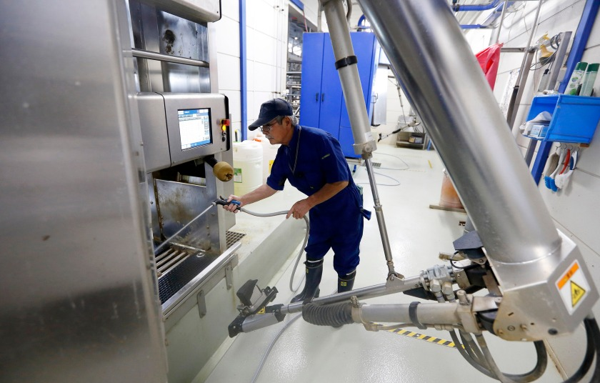 An employee sprays water into a DeLaval Inc. voluntary milking system at a dairy farm operated by Kalm Kakuyama K.K. in Ebetsu, Hokkaido, Japan, on Tuesday, Sept. 6, 2016. On the northern island of Hokkaido, Japan's top dairy-producing region, Jin Kawaguchiya transformed the 20-cow farm he inherited from his father-in-law 16 years ago into Asia's largest automated milking factory. Robots extract milk from 360 cows three times a day and make sure the animals are fed and healthy. (Tomohiro Ohsumi/Bloomberg via Getty Images