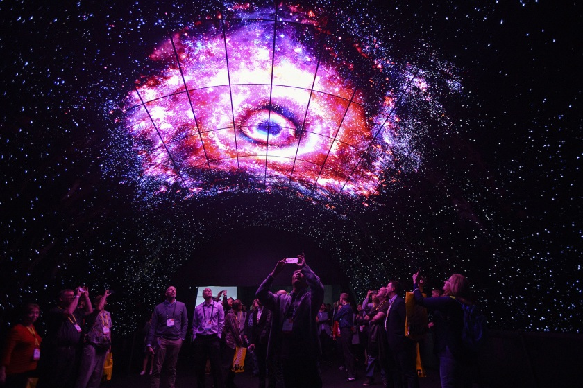 Attendees take photographs with mobile devices while standing under a tunnel wall of LG OLED 4K TVs during the 2017 Consumer Electronics Show (CES) in Las Vegas, Nevada, U.S., on Thursday, Jan. 5, 2017. CES, celebrating its 50th year, will showcase self-driving cars, TVs, drones, robots and a slew of other gadgets. Photographer: Patrick T. Fallon/Bloomberg via Getty Images