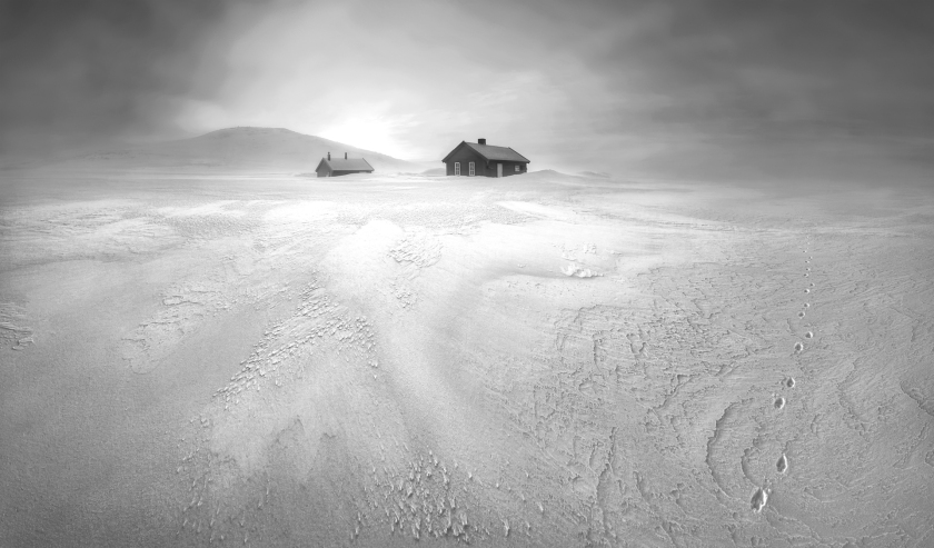 """""""After days of frigid snowstorms, a break in the weather revealed an otherworldly landscape near these hunters' cabins. The little footprints were left behind by a lone arctic fox during its relentless search for food in this barren wilderness. After scouting this frozen scene before sunrise, I discovered a spot with a snowdrift leading into the light. The placement of the hill to the left and the tracks made for a balanced image. The image is captured in a wide panoramic format to convey the vastness of the surroundings. I captured the image just before the sun broke the horizon, making for a softly lit scene that helps the textures come alive."""" (Stian Nesoy )"""