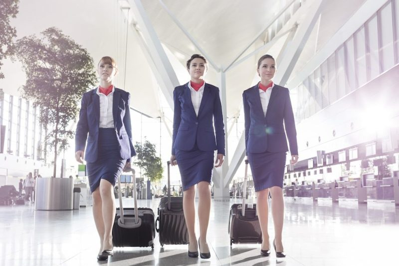 Three stewardesses with baggage walking at the airport