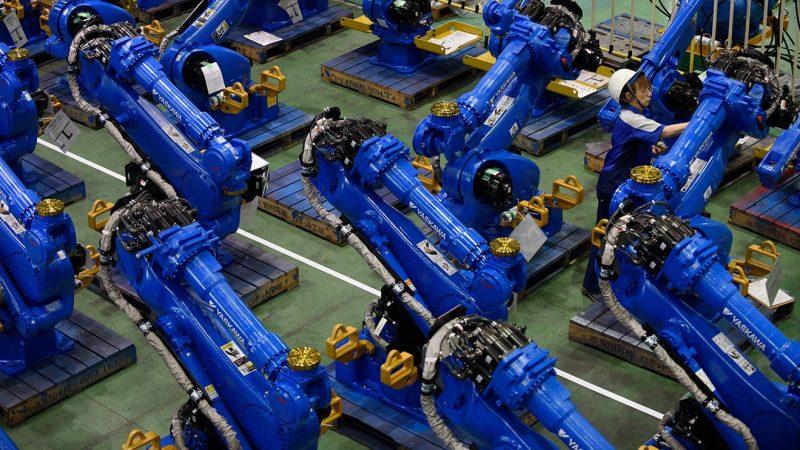 An employee inspects Yaskawa Electric Corp. Motoman robots bound for shipment at the company's factory in Kitakyushu, Japan, on Thursday, July 16, 2015. (Akio Kon/ Bloomberg)