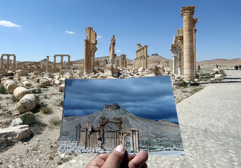 A general view taken on March 31, 2016 shows a photographer holding his picture of the Arc du Triomphe (Triumph's Arch) taken on March 14, 2014 in front of the remains of the historic monument after it was destroyed by Islamic State (IS) group jihadists in October 2015 in the ancient Syrian city of Palmyra. (Joseph Eid/AFP/Getty Images)