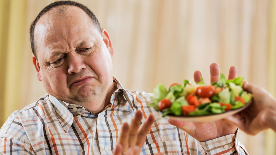Fat man refusing salad from unrecognizable person.
