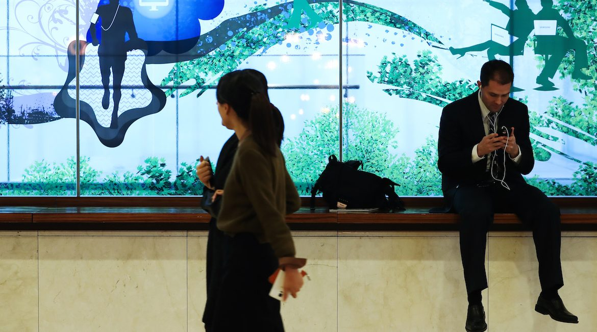 A man uses a smartphone while sitting in front of an advertisement for Samsung Electronics Co. in the COEX mall in Seoul, South Korea, on Wednesday, Jan. 4, 2017. Samsung is scheduled to release earnings results on Jan. 6. Photographer: SeongJoon Cho/Bloomberg