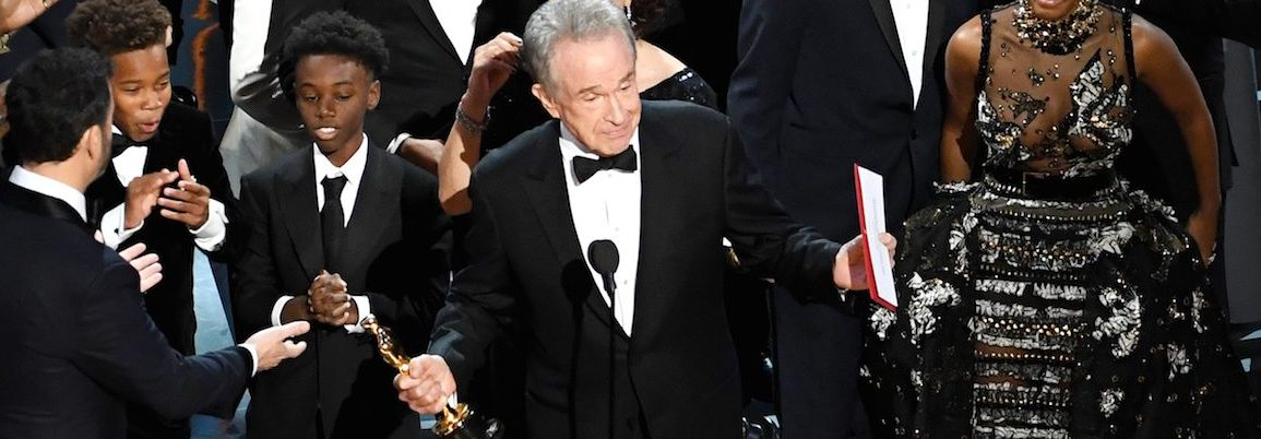 Actor Warren Beatty (C) explains a presentation error which resulted in Best Picture being announced as 'La La Land' instead of 'Moonlight' onstage during the 89th Annual Academy Awards at Hollywood & Highland Center on February 26, 2017 in Hollywood, California.  (Photo by Kevin Winter/Getty Images)