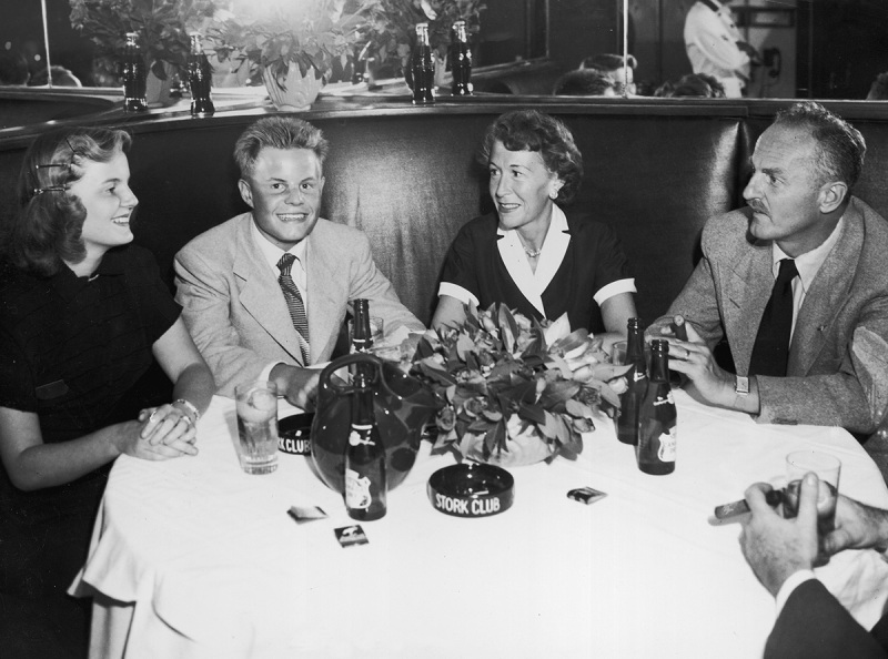 American film executive, producer, screenwriter and director Darryl F Zanuck (right), sits beside his wife, Virginia Fox Zanuck, and their two children, Darrylin and Richard Darryl, in a booth at the Stork Club in New York City. (Hulton Archive/Getty Images)