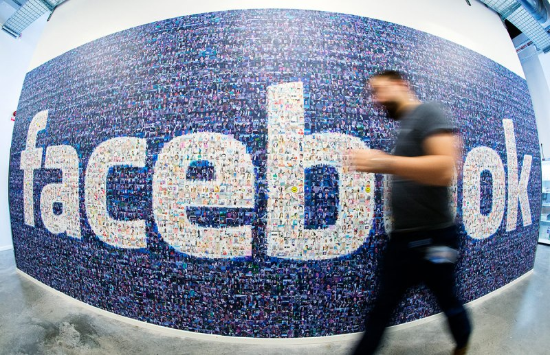 This picture taken with a fisheye lens shows a man walks past a big logo created from pictures of Facebook users worldwide in the company's Data Center, its first outside the US on November 7, 2013 in Lulea, in Swedish Lapland. The company began construction on the facility in October 2011 and went live on June 12, 2013 and are 100% run on hydro power. (Jonathan Nackstrand/AFP/Getty Images)