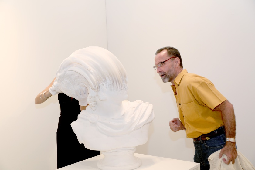 A guest enjoys the artwork by Li Hongbo on display attends the Art Miami 2016 VIP Preview at Art Miami Pavilion on November 29, 2016 in Miami, Florida. (Aaron Davidson/Getty Images for Art Miami)