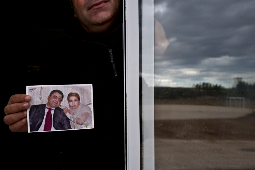 """In this Thursday, Jan. 5, 2017 photo, Henef Slu, 37, a Syrian refugee from Aleppo's northern district of Sheikh Maqsud, holds a photograph of his wedding day, from the window of his shelter in Ritsona refugee camp, Greece. """"It was the most beautiful day of my life the day I married my wife Nadima, we had a lot of guests, family and friends, this photograph was the only thing we carried with us from home."""" Henef said. (AP Photo/Muhammed Muheisen)"""