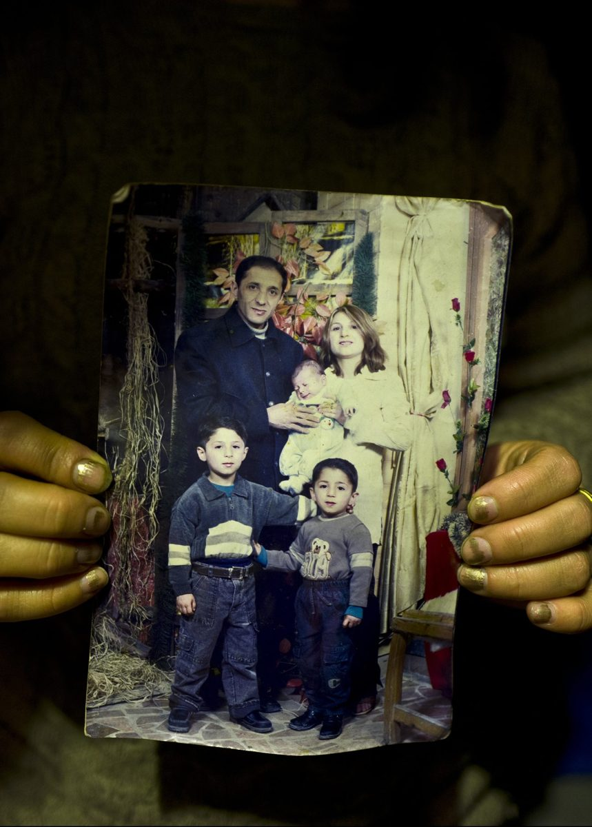 """In this Thursday, Jan. 19, 2017 photo, Fidan Kiru, 31, a Syrian refugee from Afrin, holds a photograph taken in 2004 showing herself and her husband Mohyeddin, when he was 27-year-old, and her sons, younger to older, Avindar, 8 months, Khalid, 4 and Levant, 6, at her tent in Kalochori refugee camp on the outskirts of the northern Greek city of Thessaloniki. """"This is the only group family picture we have, my husband is currently in Germany and I hope they will allow me to join him."""" Fidan said. (AP Photo/Muhammed Muheisen)"""
